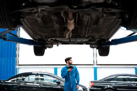 Mechanic in blue work wears uniform prepare to inspects the car bottom with a flashlight. Automobile repairing service, Professional occupation teamwork. Vehicle maintenance.