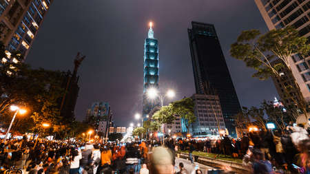 TAPEI, TAIWAN. DEC 31, 2011: Taipei City Night landscape and Taipei 101 skyscraper before lit up by fireworks. People watching and taking photos and videos around buildings to celebrate the new year.