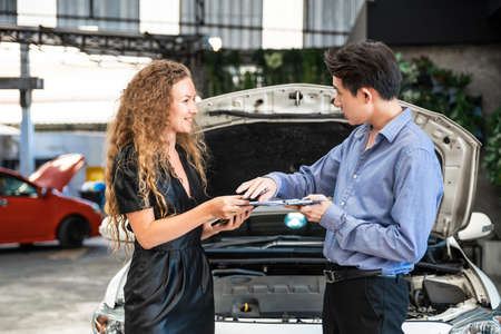 The Caucasian woman is talking with an Asian insurance officer for repair service assistance after her car was broken and opened the car hood. Automobile emergency service to fix the problem. 版權商用圖片