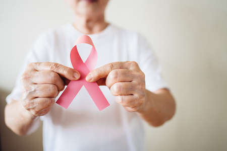 Senior woman supports Breast Cancer Day by holding Pink Ribbon Breast Cancer Awareness with copy space. Healthcare and medicine concept. October Pink day. World Cancer Day.