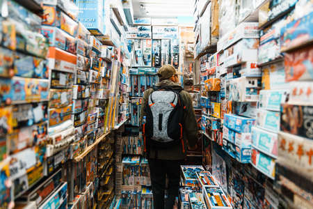 TAIWAN, TAIPEI. DEC 31, 2017: Tourist walking amid Gunpla, Gundam and vehicle (Car, Motorcycle, Truck, Tank, etc.) plastic model kit boxes on the shelf in the retail shop.