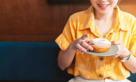 Woman smile and wearing yellow shirt holding and showing a pale green plate of sugar glazed donut in a modern cafe. Enjoyment female lifestyle. Focus on hand and donut.