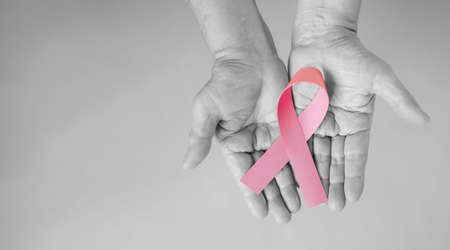 Senior woman hands in black and white support Breast Cancer Day by holding Pink Ribbon Breast Cancer Awareness with copy space. Healthcare and medicine concept. October Pink day. World Cancer Day. 版權商用圖片