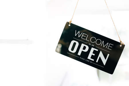 Welcome and Open sign board through the glass of door in the cafe with clear interior white background and copy space. Cafe open status and ready to service. Business service and food concept.