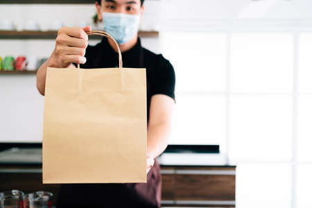 Male barista showing takeaway coffee in the paper bag during Coronavirus outbreak time. A worker inside the cafe counter for online delivery service. Coffee paper bag mockup. Archivio Fotografico