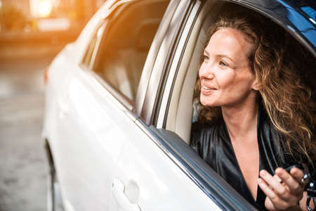 Caucasian beautiful female with a little smile sitting inside the car and looking outside car window. Automobile rental and leasing business. Optimistic friendly woman.