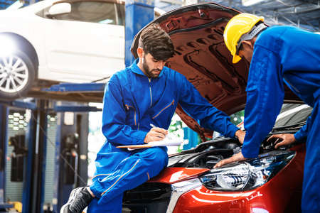 Mechanic checking the opened hood car with his assistant. Auto car repair service center. Professional service.