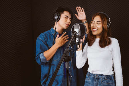 Pretty Asian female and male singer recording songs by using a studio microphone and pop shield on mic with passion in music recording studio. Performance and show in the music business. Duet session.