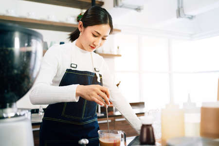 A female barista student attentively measured and added milk in the coffee while the teacher watching her in the coffee shop. Coffee making classes for entrepreneurs to start small businesses. 免版税图像 - 157999358