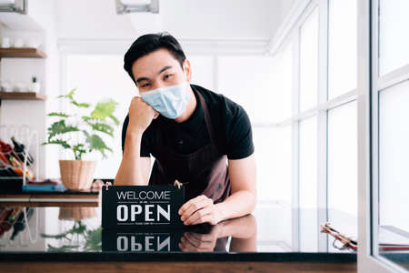 "Young male barista cafe owner wearing a face mask, standing inside the coffee counter and holding the ""OPEN"" announcement board. People's lifestyles during Covid-19 pandemic."