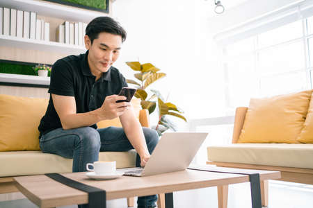 Asian male looking at a mobile phone while sitting and working with laptop on the table. Businessman working on laptop at home, Working in a relax area in the office. Business quarantine period.