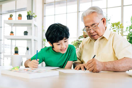 Asian retirement grandfather and his grandson spending quality time together insulated at home. Enjoy drawing with colored pencils. Family bonding between old and young. Concept of quarantine.