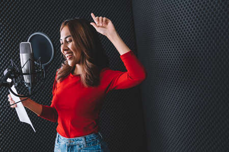Pretty Asian female singer recording songs by using a studio microphone and pop shield on mic with passion in music recording studio. Performance and show in the music business. Image with copy space. Banque d'images
