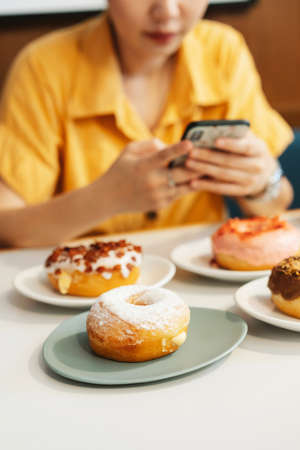 Woman wearing yellow shirt taking photos of strawberry pink, chocolate, sugar glazed and bacon, cheese donut with feeling happy a modern cafe. Enjoyment female lifestyle. Stock fotó
