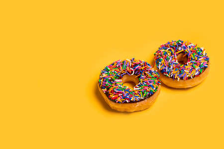 Two of chocolate frosted donuts with sprinkles on yellow background. Playful and joyful tasty sugary comfort food for customers with copy space.