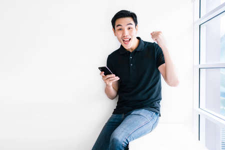 Good looking Asian male wearing a casual look at the camera while using a mobile phone and give a victory fist, sitting near the window with natural light. Modern technology supports the business.