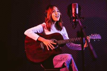 Pretty Asian female singer recording songs by using a studio microphone and pop shield on mic while playing guitar and wearing headphones in the studio. Performance and show in the music business.