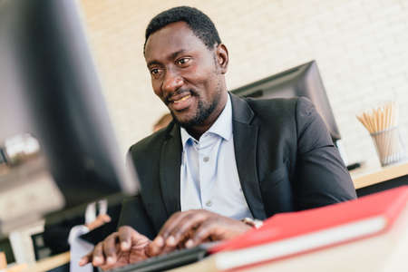 The African businessman typing keyboard and looking on the screen with a smile and happy mood at his desk workplace with copy space.