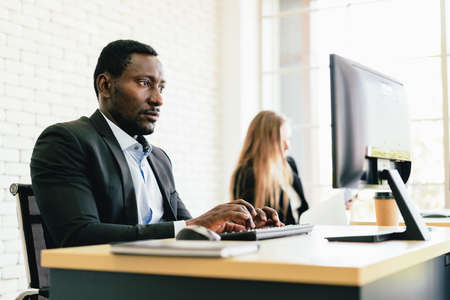 The African businessman typing keyboard and looking on the screen with intention at his desk workplace with copy space.