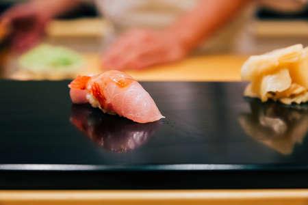 Japanese Omakase in Edo Style: Close up Otoro (Fatty Tuna) Sushi served on glossy black plate. Japanese traditional luxury meal.
