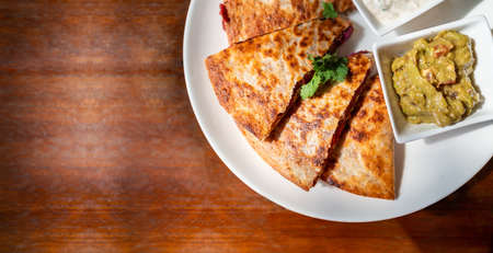 Crop image top view of Vegan Quesadilla: grilled whole-wheat tortilla filled with sweet potato and red bean, vegan quesso cheese served with guacamole salsa and Tzaziki sauce. 免版税图像