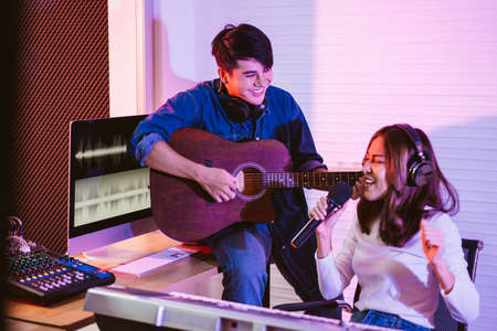 Pretty Asian female singer recording songs by using a studio microphone with male playing guitar in blue and red light. Performance and show in the music business. Duet session. 免版税图像