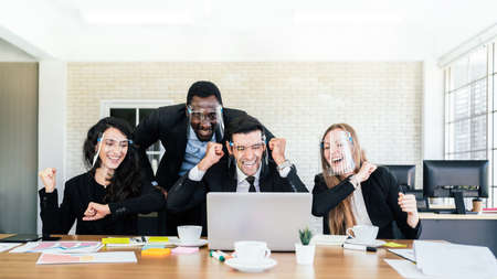 African businessman stands in the back of Caucasian colleagues wearing face shield. looking on laptop at business group meeting with success and happiness mood. Cooperation group ideas discussion.