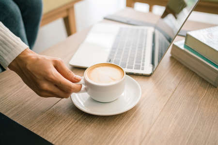 Crop image of a woman hand wearing a sweater holding a morning cup of hot latte coffee, laptop and novels on a wooden working table. Work from home concept. Quarantine period. 免版税图像