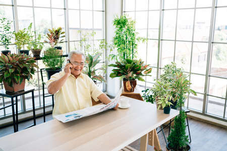 An Asian senior retired man in casual clothes using a mobile with a smile while reading a newspaper. While sitting at home with an indoor garden. Retirement hobby and lifestyle. 免版税图像