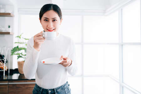 A Young pretty Asian female wearing a sweater drinking a hot coffee in a white ceramic cup with a smile near the glass window with copy space.