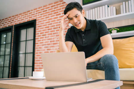 Asian male in casual feels stress and concerned with laptop while working and sitting on the sofa. Businessman working with problems on a laptop at home. Solving the problem process in business. 免版税图像