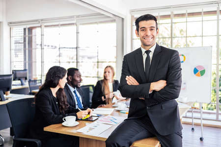 Caucasian confident businessman smile in good mood, sitting on a meeting table with a diverse colleague in the back. Businesspeople of various nationalities such as Caucasian and African people.