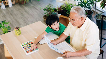 Above view of Asian retirement grandfather and his grandson spending quality time together insulated at home. Enjoy drawing with colored pencils. Family bonding between old and young.