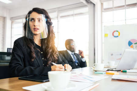 Caucasian businesswoman wearing face shield, sitting at meeting table with notebook, pen and tablet with blur African businessman in the background with copy space. Legal partnership consultant.