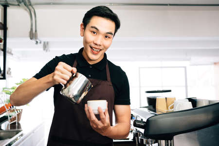 Young Asian male barista looking at the camera, wearing an apron pouring hot milk into hot espresso black coffee for making Latte Art. 免版税图像