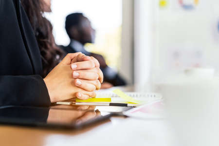 Close-up Caucasian businesswoman hands holding together on meeting table with notebook, pen and tablet with blur African businessman in the background with copy space. Legal partnership consultant.