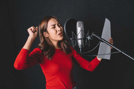 Pretty Asian female singer recording songs by using a studio microphone and pop shield on mic with passion in music recording studio. Performance and show in the music business. Image with copy space. 免版税图像 - 163627164