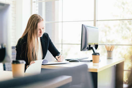 Portrait of attractive Caucasian businesswoman analyzing and writing notes on the papers on the office table with a monitor. Secretary job analysis and assistant for the executive manager.