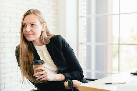 Portrait of attractive Caucasian businesswoman holding a coffee cup and intentionally listening to another employee with copy space. Secretary job analysis and assistant for the executive manager.
