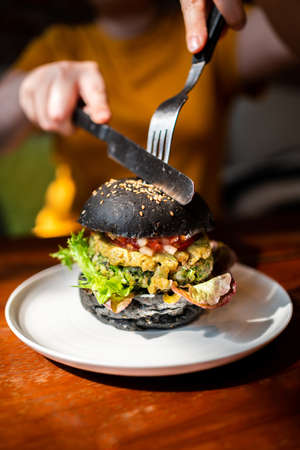 Hands cuts Broccoli quinoa charcoal burger topped with guacamole, mango salsa and fresh salad by knife and fork, served in a white plate. Creative vegan meal for vegetarians. 免版税图像