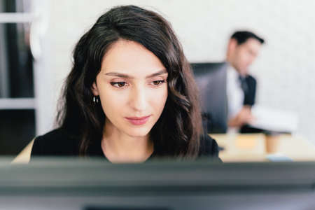 Close-up portrait of a Caucasian businesswoman typing and looking on a computer screen with intention at her desk. Concern and fix problems in a corporate office.
