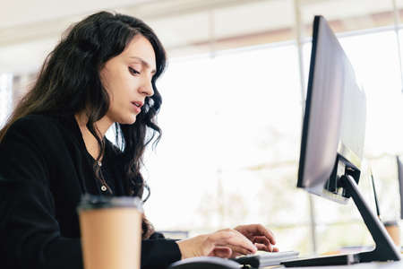 The portrait of a Caucasian businesswoman typing keyboard and looking on keyboard and computer screen with intention at her desk. Concern and fix problems in a corporate office.