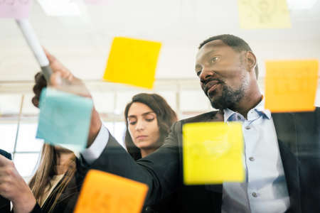 Close-up of smiling African businessman brainstorm meeting with colleagues by using colorful sticky paper note on glass wall for finding new ideas. Using agile methodology and do business.
