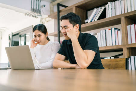 The nervous Asian male and female sitting in front of a laptop, looking with a bad and uncomfortable feeling. Reklamní fotografie