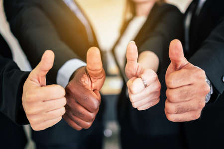 Close up of a group of diverse businesspeople showing raised thumbs at the camera. Recommendation of good choice. The diversity of African and Caucasian businesspeople gives a positive response. Reklamní fotografie