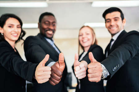 A group of diverse businesspeople showing raised thumbs at the camera. Recommendation of good choice. The diversity of African and Caucasian businesspeople gives a positive response. Focus on thumbs.