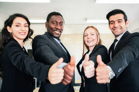 A group of diverse businesspeople showing raised thumbs at the camera. Recommendation of good choice. The diversity of African and Caucasian businesspeople gives a positive response. Focus on people. Reklamní fotografie
