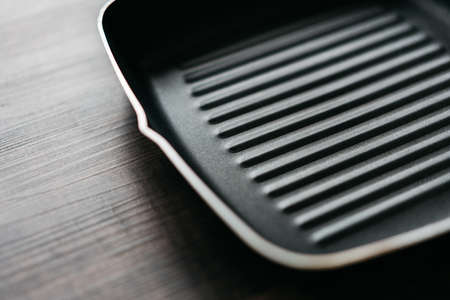 Close-up the empty non-stick square frying pan over wooden kitchen counter background with copy space.