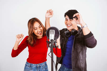 Pretty Asian female and male singers recording songs by using a studio microphone and pop shield on the microphone with passion in music recording studio white background. Duet session.