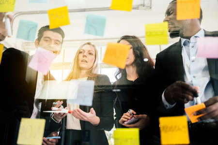 Group of successful business teamwork. Brainstorm meeting with colorful sticky paper note on glass wall for new ideas. Using agile methodology and do business. Brainstorming in a tech start-up office. Reklamní fotografie